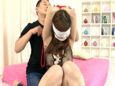 Blindfolded Akimi lies on her belly and gets her hairy cunt tickled